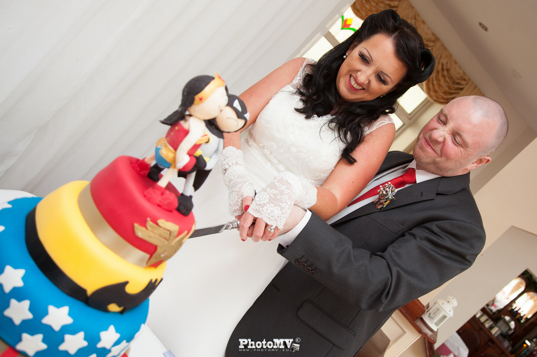 cutting superhero wedding cake