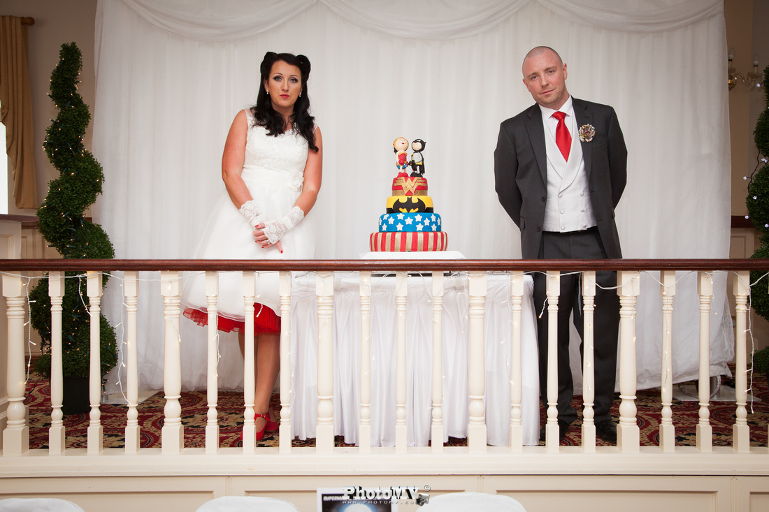 Superhero wedding cake and bride and groom beside it