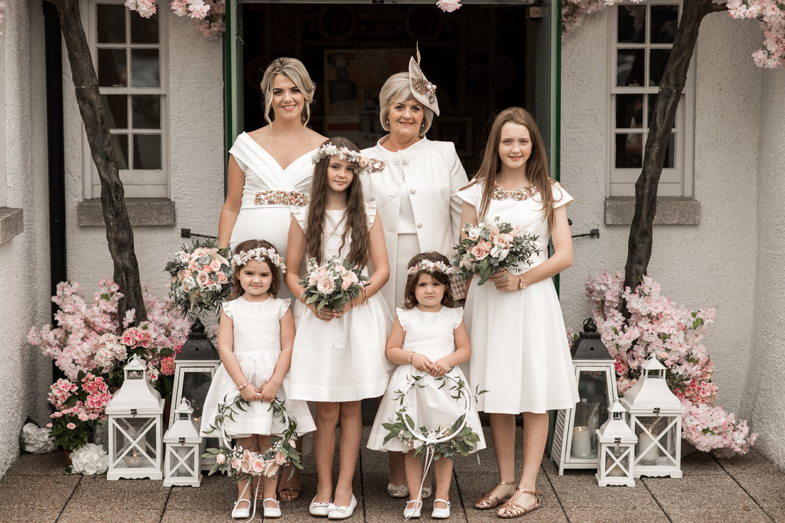 Stunning white dresses for bridesmaids, mom and flower girls. Photographer Mario