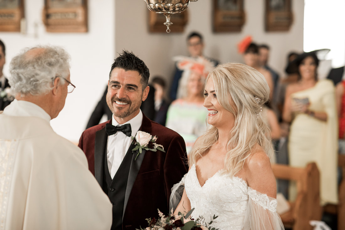 Bride and groom greets priest in a wedding in Carlingford
