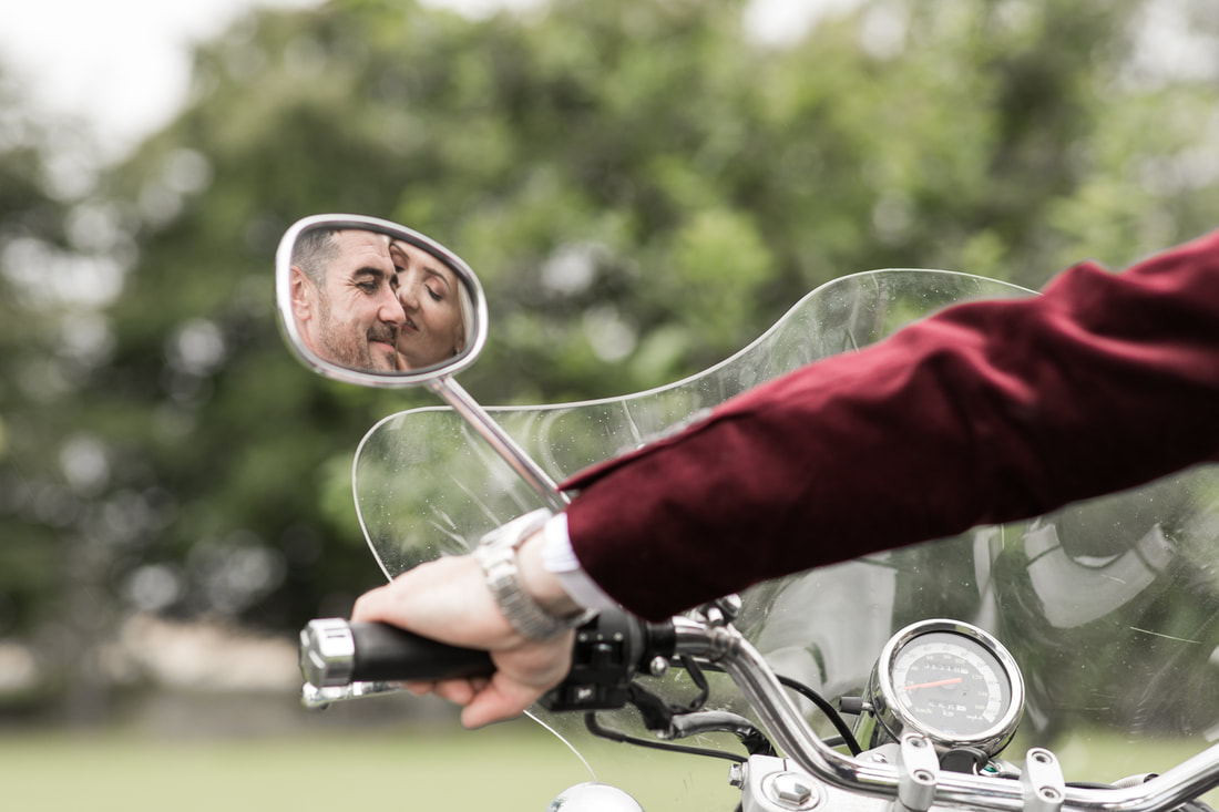 Bride and groom kissing, reflection on a bikes mirror. Creative wedding photographer in Dundalk