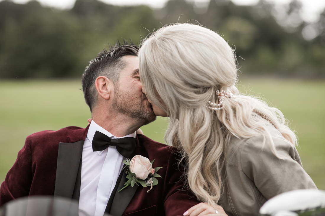 Bride and groom kissing on a bike