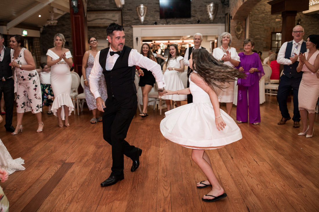 Groom dances with his daughter at a wedding