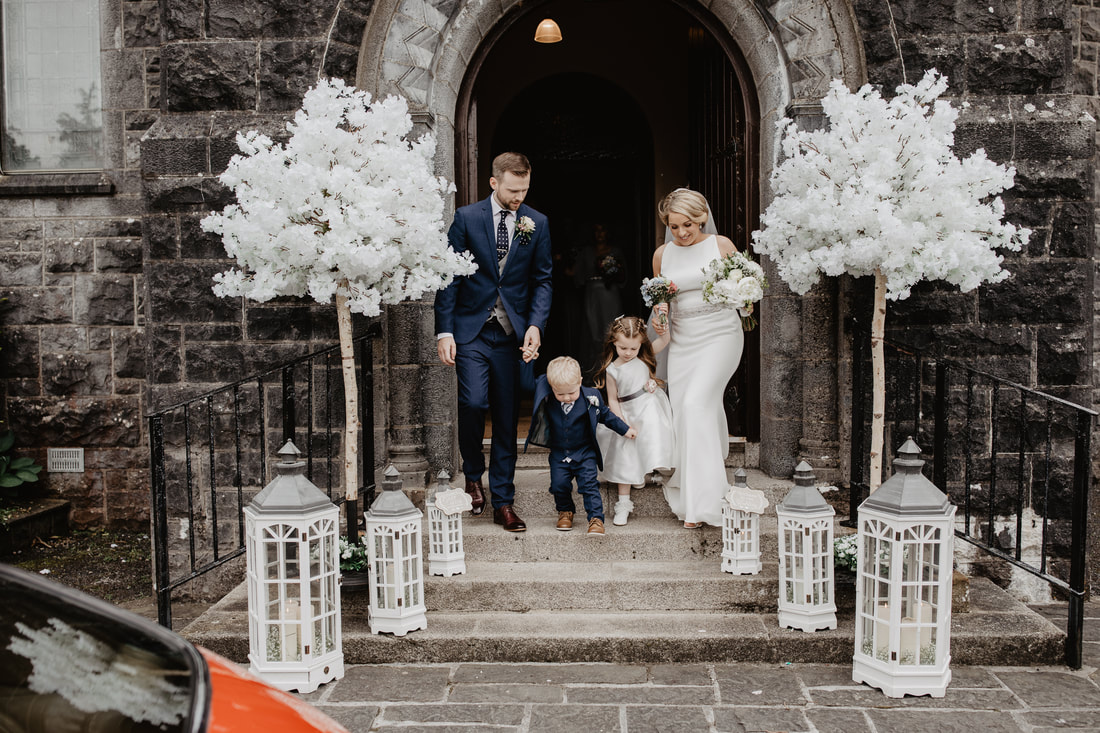 Wedding decor at a church, bride and groom exit. with their kids. Lovely white sakura trees. Best wedding photographer in Galway