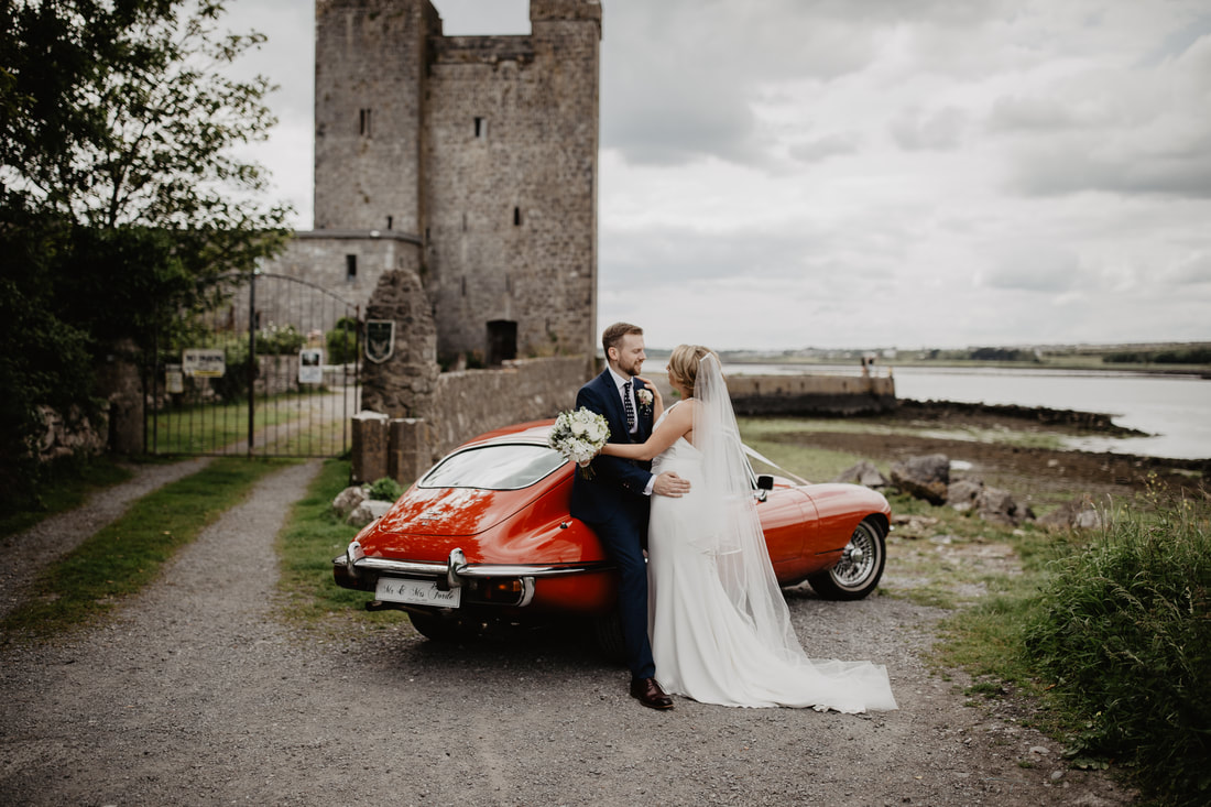 Red Jaguar E type  and bride and groom. Vintage wedding car. Photographer Mario