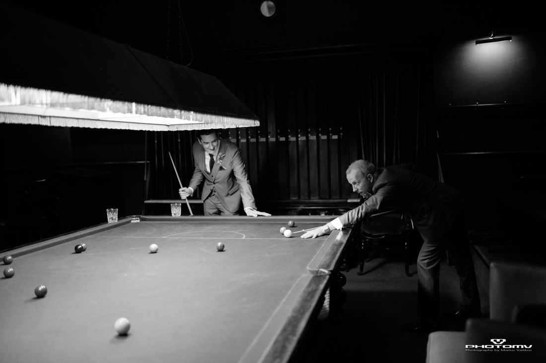 Gay couple play pool at a wedding. Gay wedding photography by Mario Vaitkus