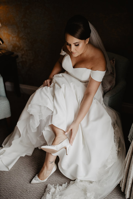 Getting into a wedding dress, at Clanard Court Hotel, Athy, Co. Kildare by wedding photographer Mario Vaitkus