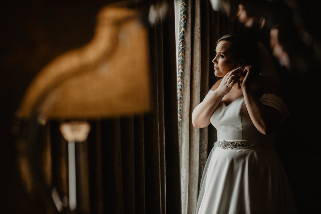 Bride in front of the window at Clanard Court Hotel, Athy, Co. Kildare by wedding photographer Mario Vaitkus