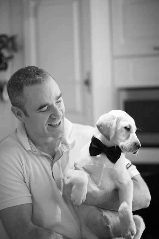Grooms present a puppy. Candid warm photo